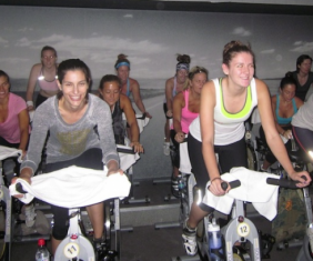 Samantha (right) smiles and spins right before the big reveal. (Photo courtesy of SoulCycle)