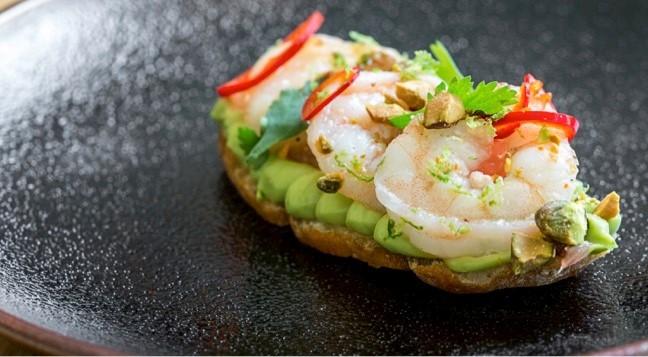 bread with avocado shrimp pistachios on black plate