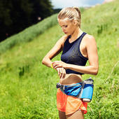Woman exercising outside, checking watch