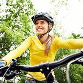 Woman mountain biking, smiling